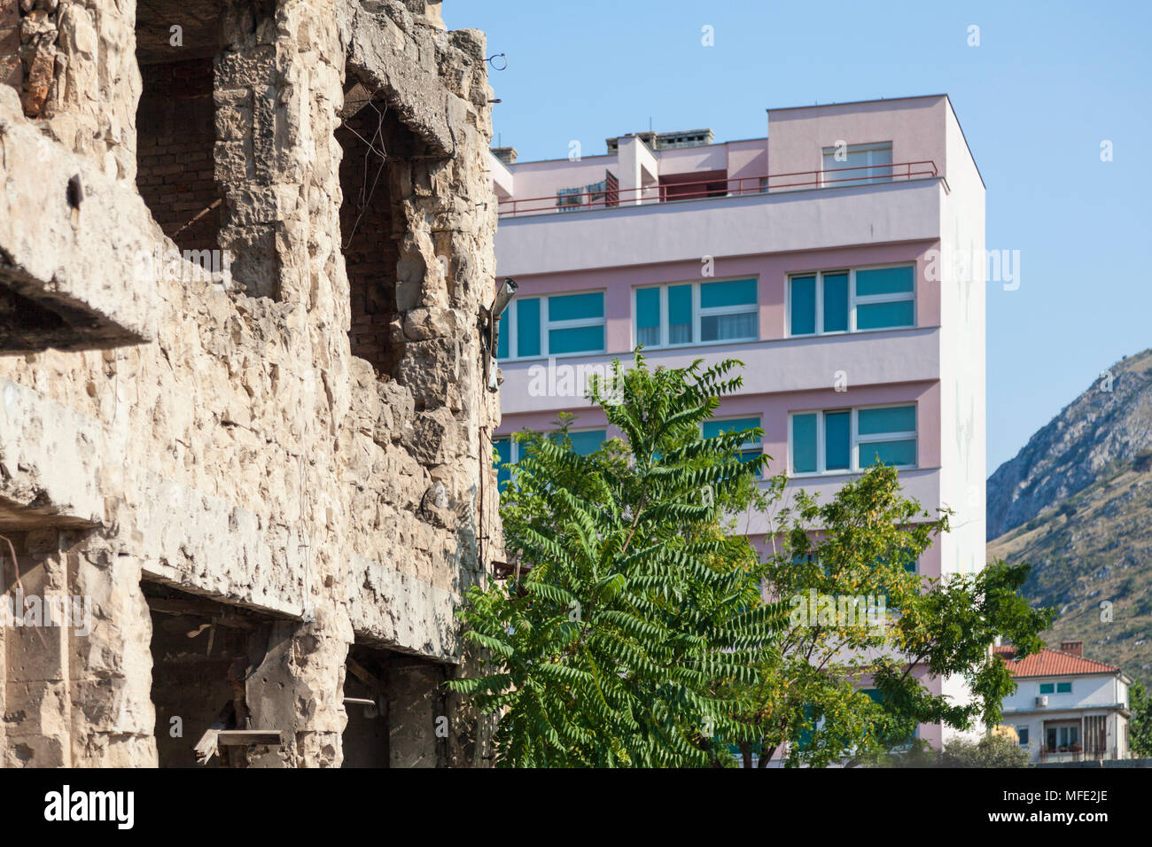 A bombed out building from the Bosnian War next to a new building in Mostar, Bosnia and Herzegovina - Stock Image
