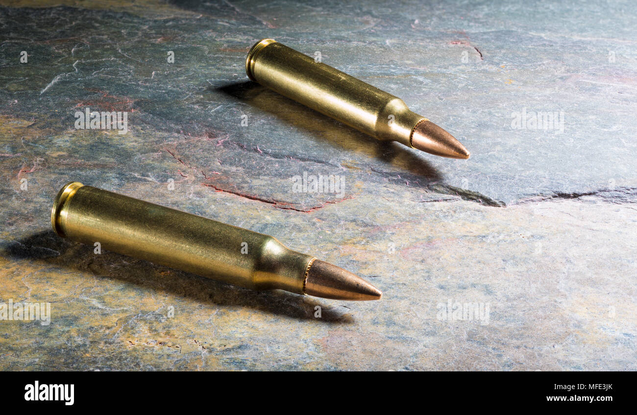 Cartridges on a dark rock that are designed for an assault rifle Stock Photo