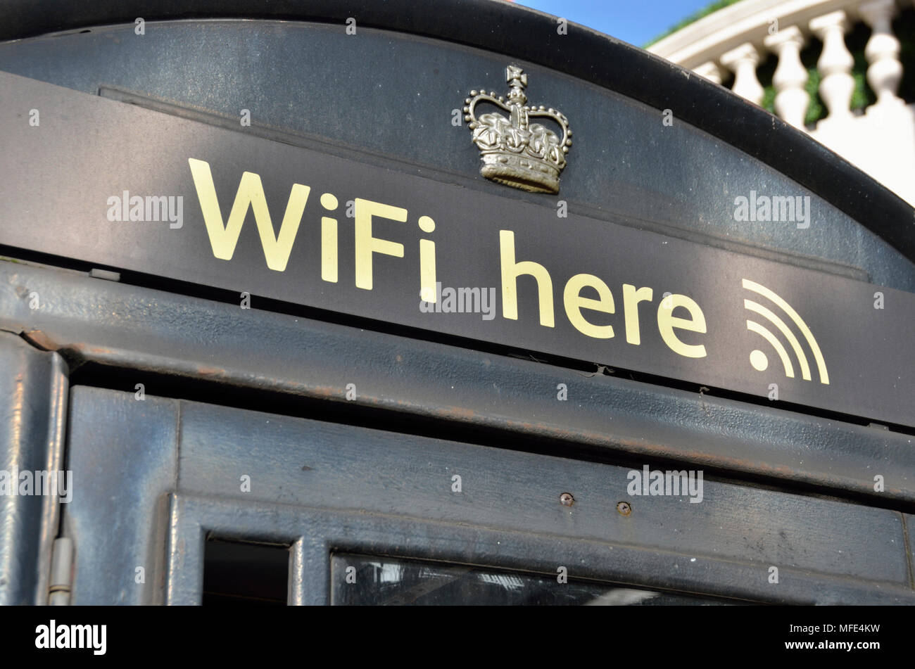 'Wifi here' sign on a public telephone box - Stock Image