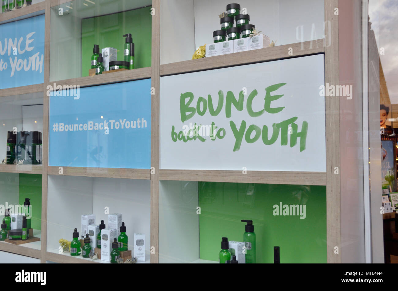'Bounce back to Youth' sign and cosmetics in a shop window - Stock Image