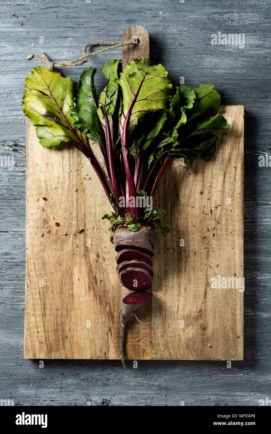 high angle view of a chopped raw beetroot on chopping board, placed on a gray rustic wooden table - Stock Image