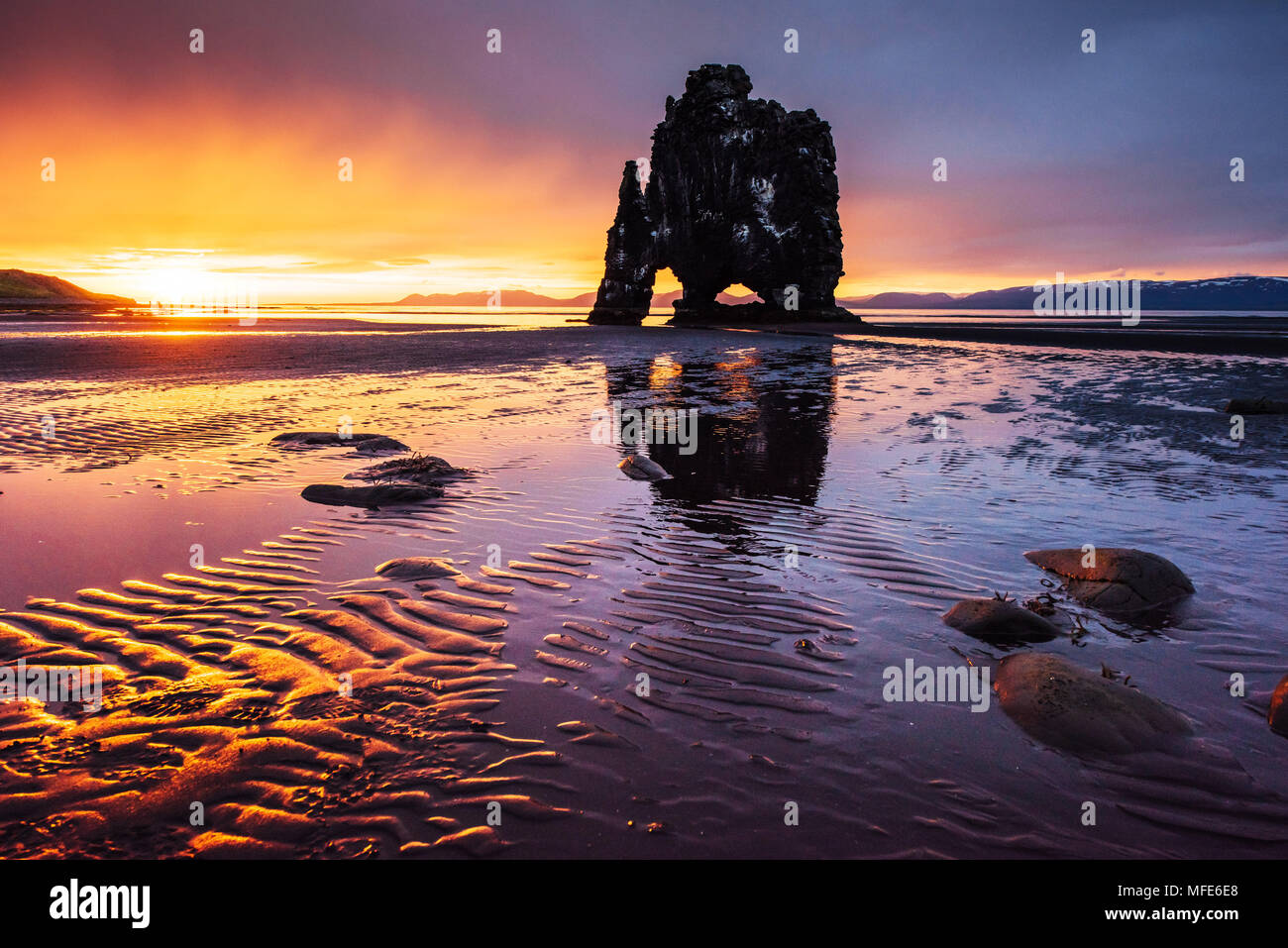 Is a spectacular rock in the sea on the Northern coast of Iceland. Legends say it is a petrified troll. On this photo Hvitserkur reflects in the sea water after the midnight sunset - Stock Image