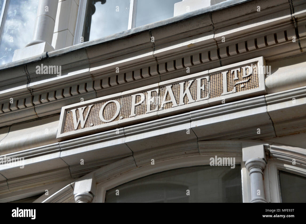 W O Peake Ltd carved stone sign, Radiant House, Mortimer Street, Fitzrovia, London, UK. - Stock Image
