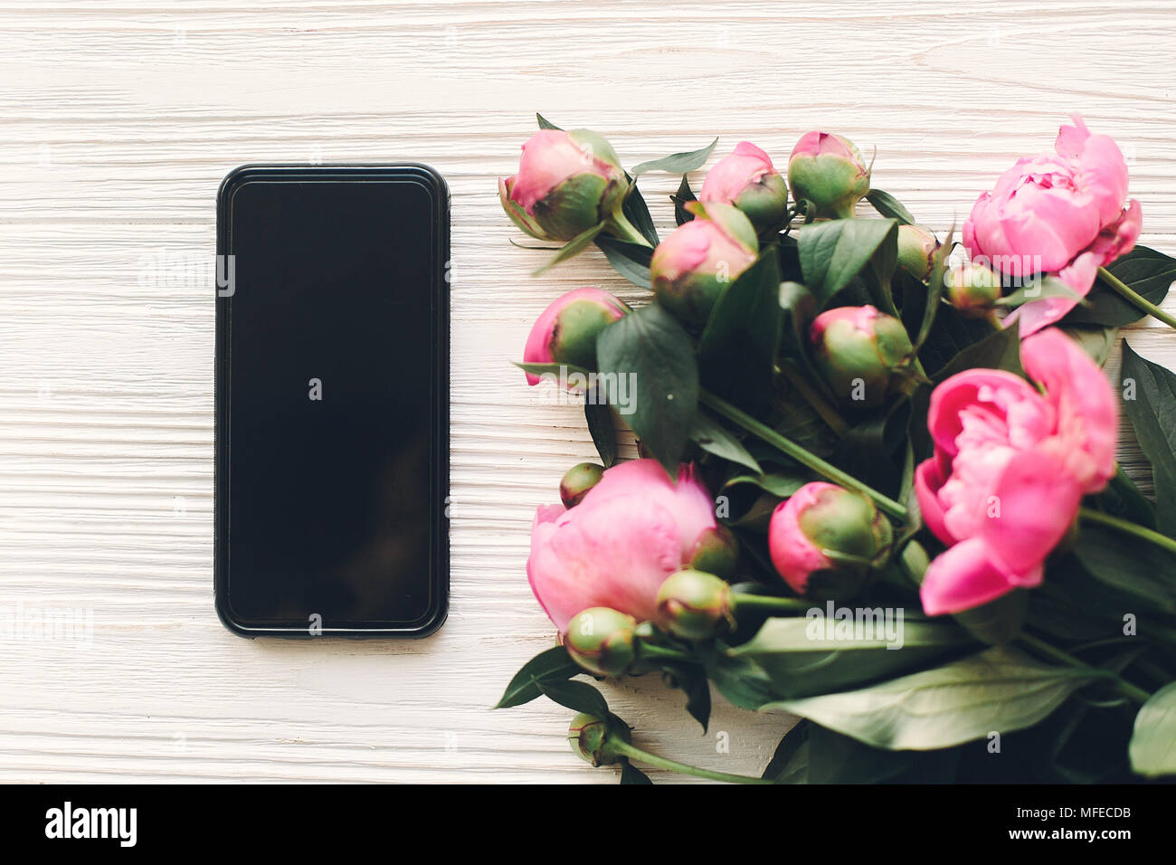 Lovely Pink Peonies And Phone With Empty Screen On Rustic White