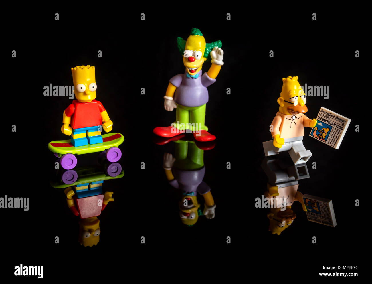 The Simpsons Lego miniature figures (Bart Simpson, Krusty the Clown and Grampa Simpson) on reflective black background - Stock Image