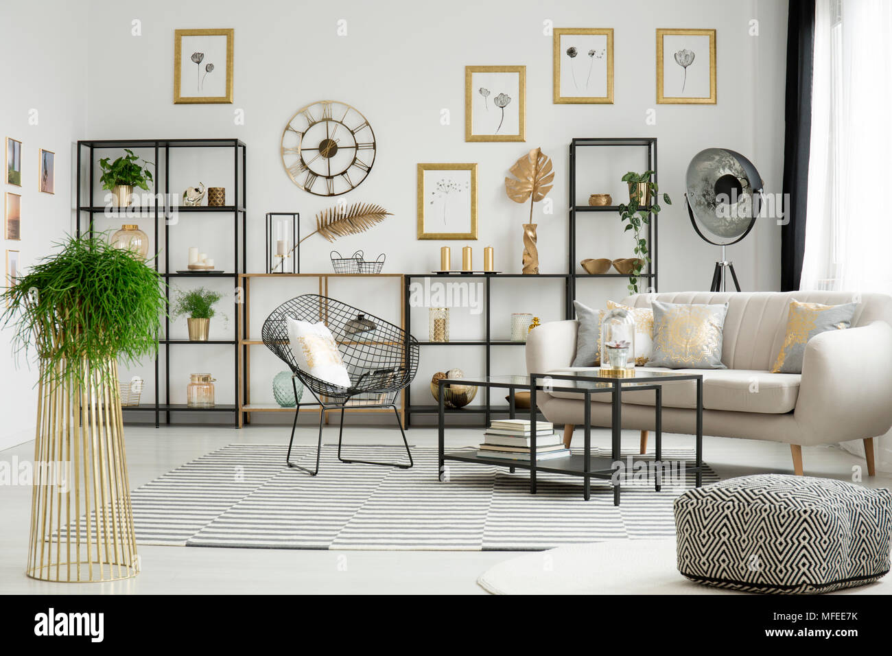 Plant and patterned pouf in spacious gold living room interior with ...