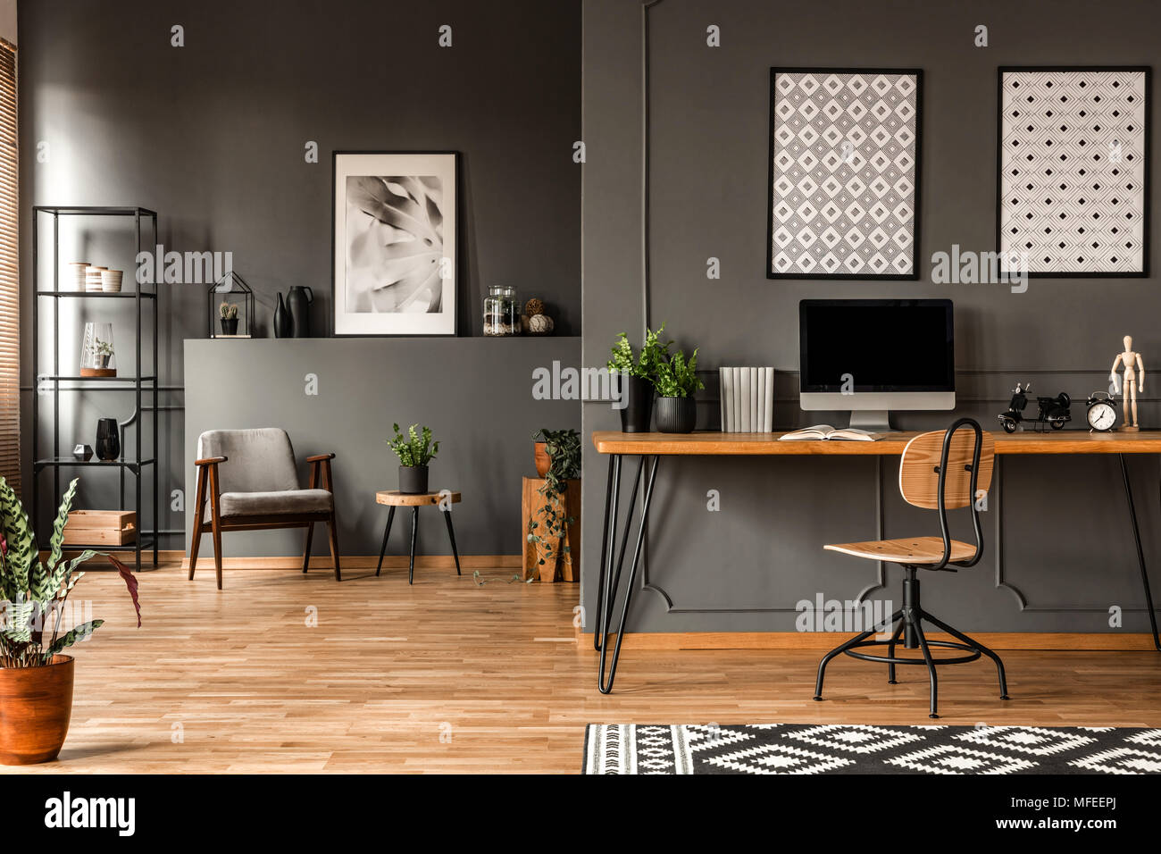 Patterned posters above desk with computer monitor in grey home office interior with plants - Stock Image