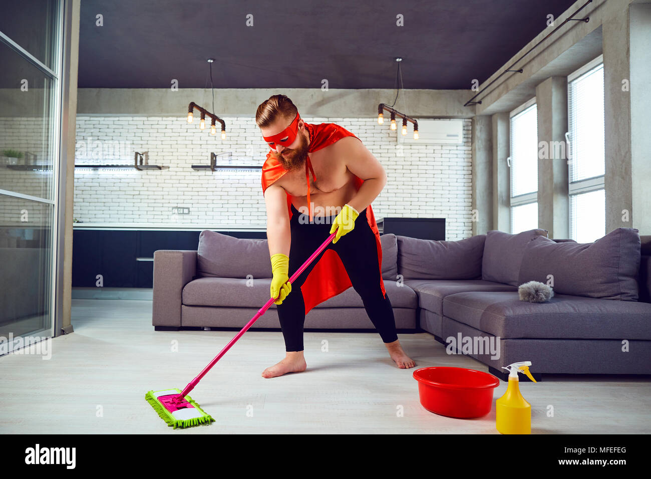 A Fat Funny Man In A Superhero Costume Is Cleaning The House Stock Photo Alamy