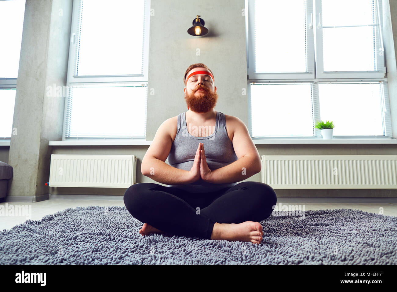 A funny fat bearded man in sports clothes does yoga in the room. - Stock Image