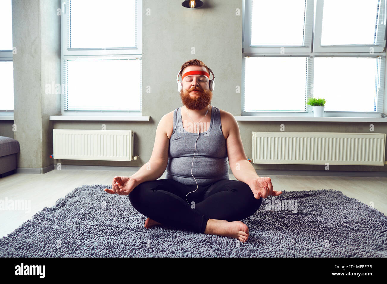 A funny fat bearded man in the headphones does yoga. - Stock Image
