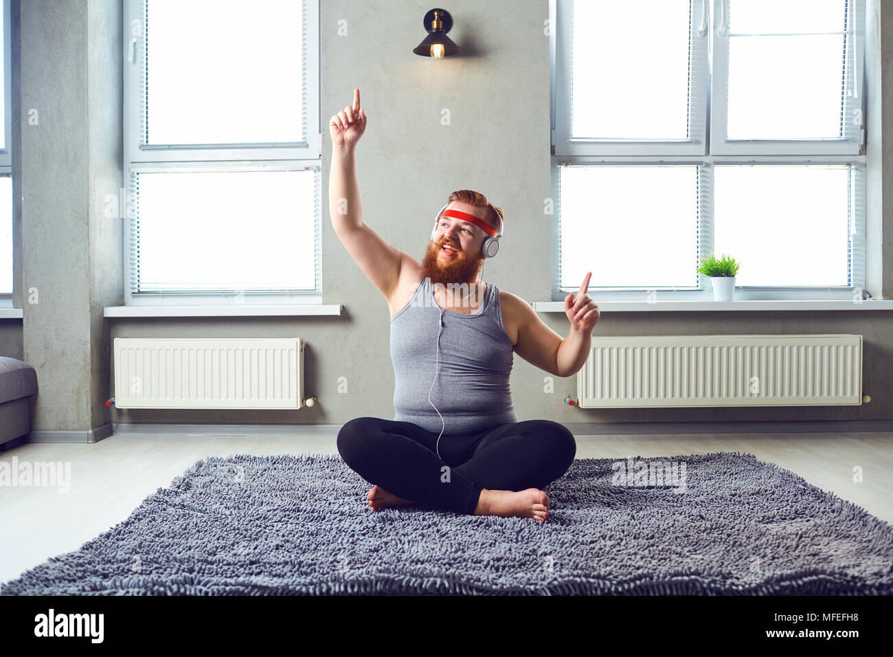 A funny fat bearded man in the headphones does yoga in the room. - Stock Image