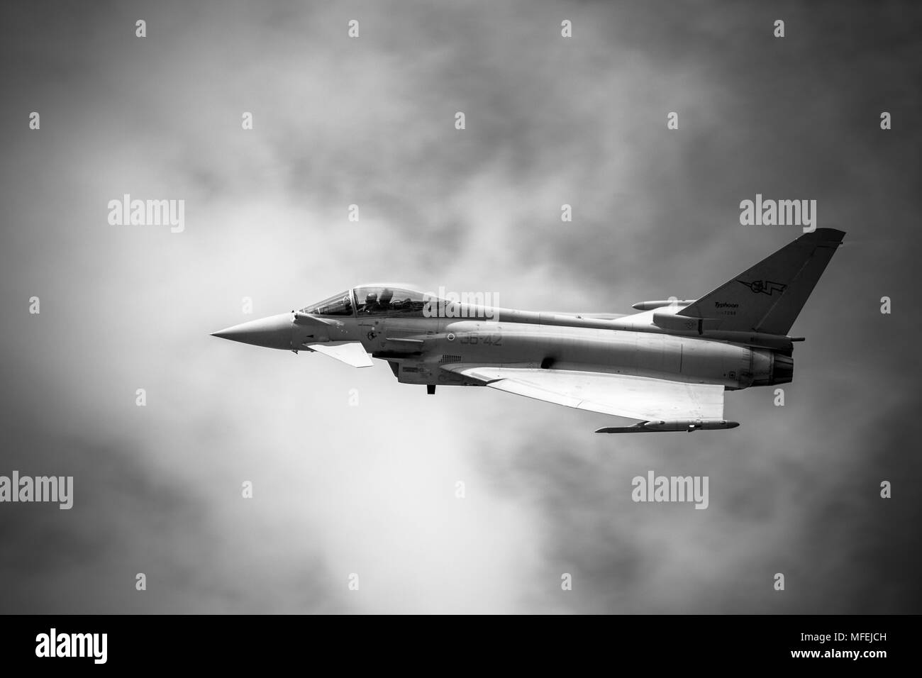A dramatic black & white low fly pass of the Italian Air Force Eurofighter Typhoon in heavy mist and cloud on a warm wet day Stock Photo