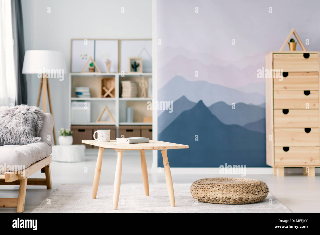 Popular Wallpaper Mountain Room - blurred-photo-of-a-scandi-living-room-interior-with-mountain-wallpaper-and-beige-sofa-focus-on-a-wooden-table-and-pouf-in-the-middle-MFEJYY  2018_25597.jpg