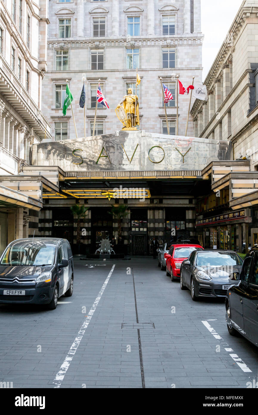 London, United Kingdom - March 27, 2015: Set back from the street is the Savoy Hotel with it's distinctive shiny chrome awning. - Stock Image