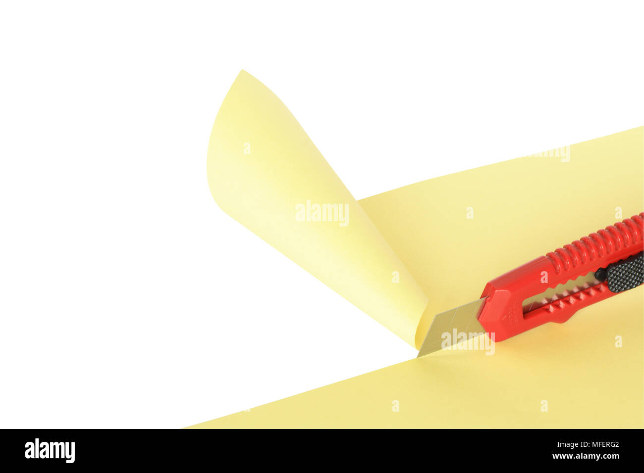 Red knife cutting yellow paper sheet. Isolated on white with clipping path - Stock Image