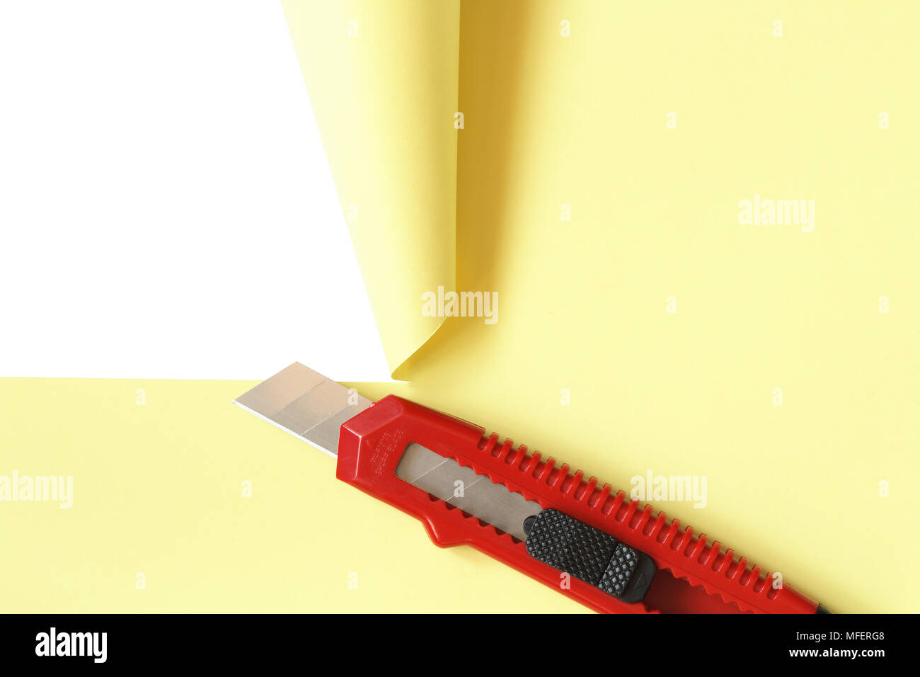 Red office knife cutting yellow paper sheet. Isolated on white with clipping path Stock Photo