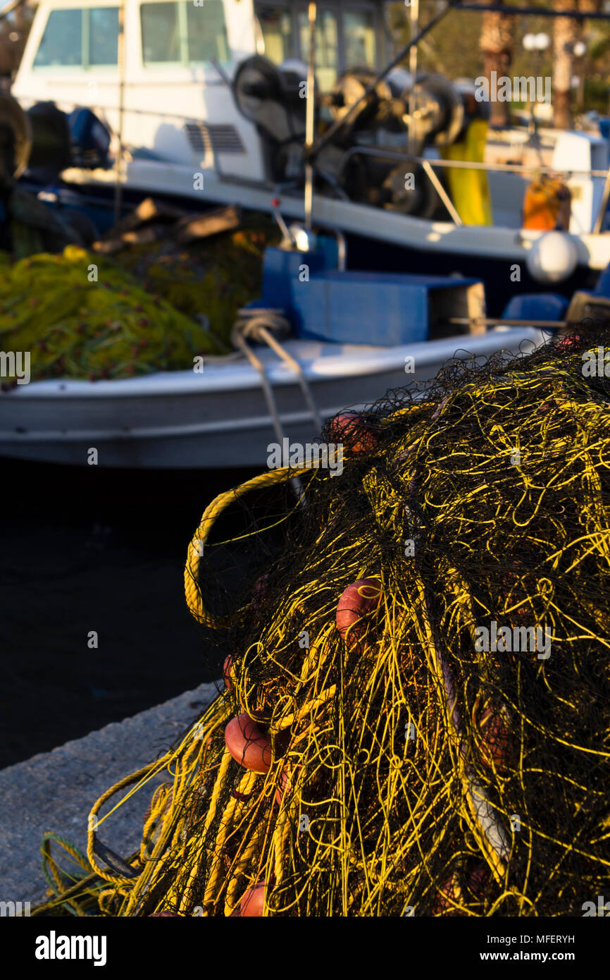 Fishing nets and fishing boats in harbor of Greek fishing village in Greek mainland. - Stock Image