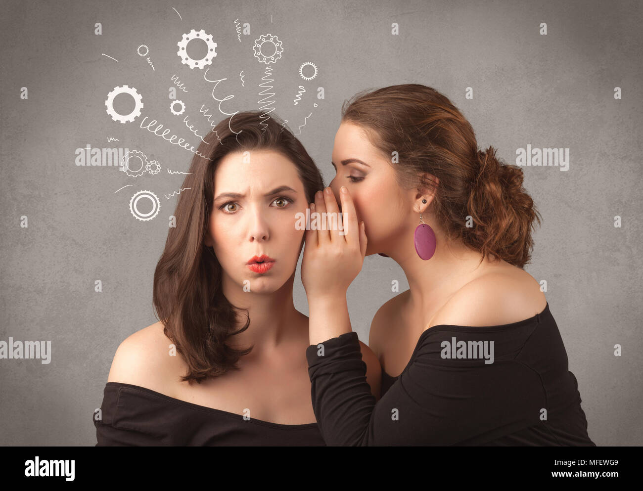 Two girlfriends in elegant black dress sharing secrets with each other concept with drawn rack cog wheels and spiral lines on the wall background. - Stock Image
