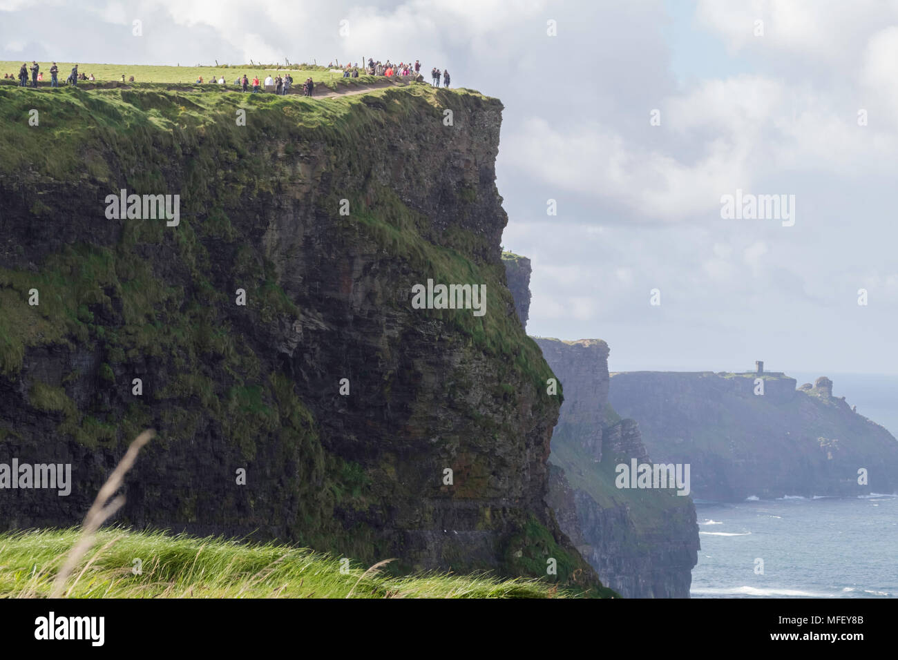 Cliffs of Moher, Ireland, Europe, closeup, tourists, daylight, clouds - Stock Image