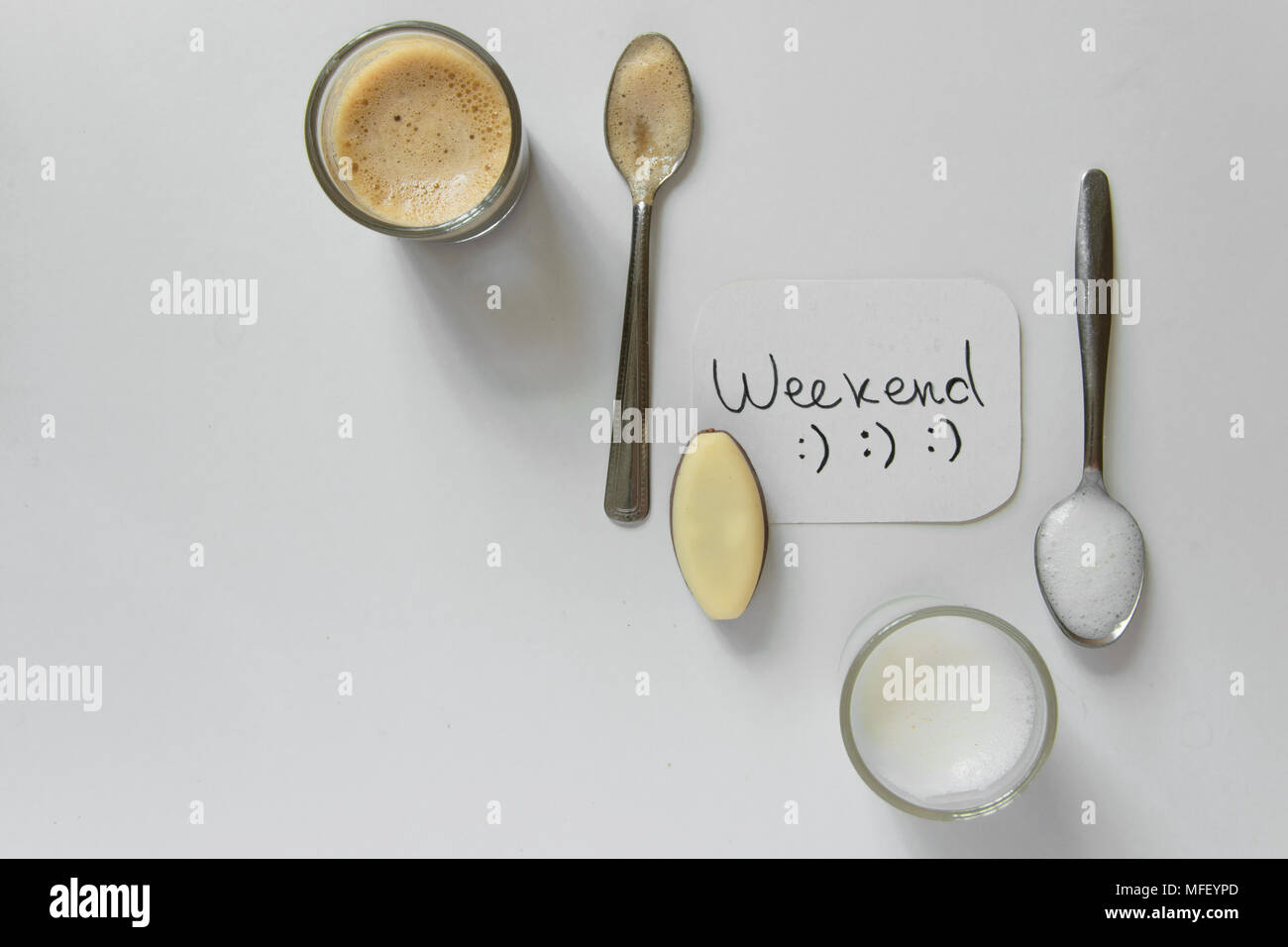 Top view of flat lay style for weekend/holiday break for two. Coffee cup, milk cup and chocolates on table, space for text - Stock Image
