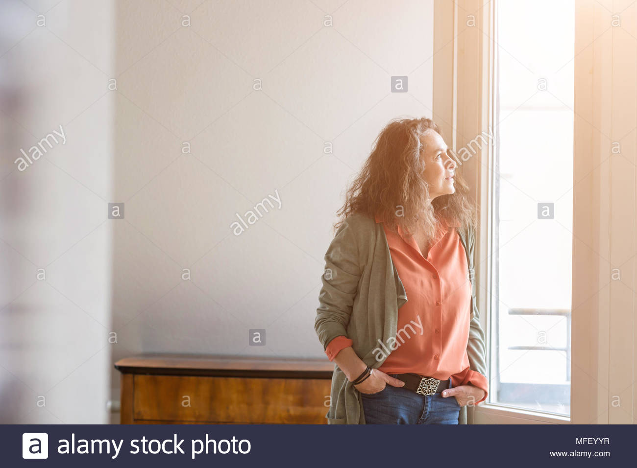 Attractive middle-aged woman standing with her hands in her pockets of her jeans staring out of a window with a thoughtful expression and copy space Stock Photo