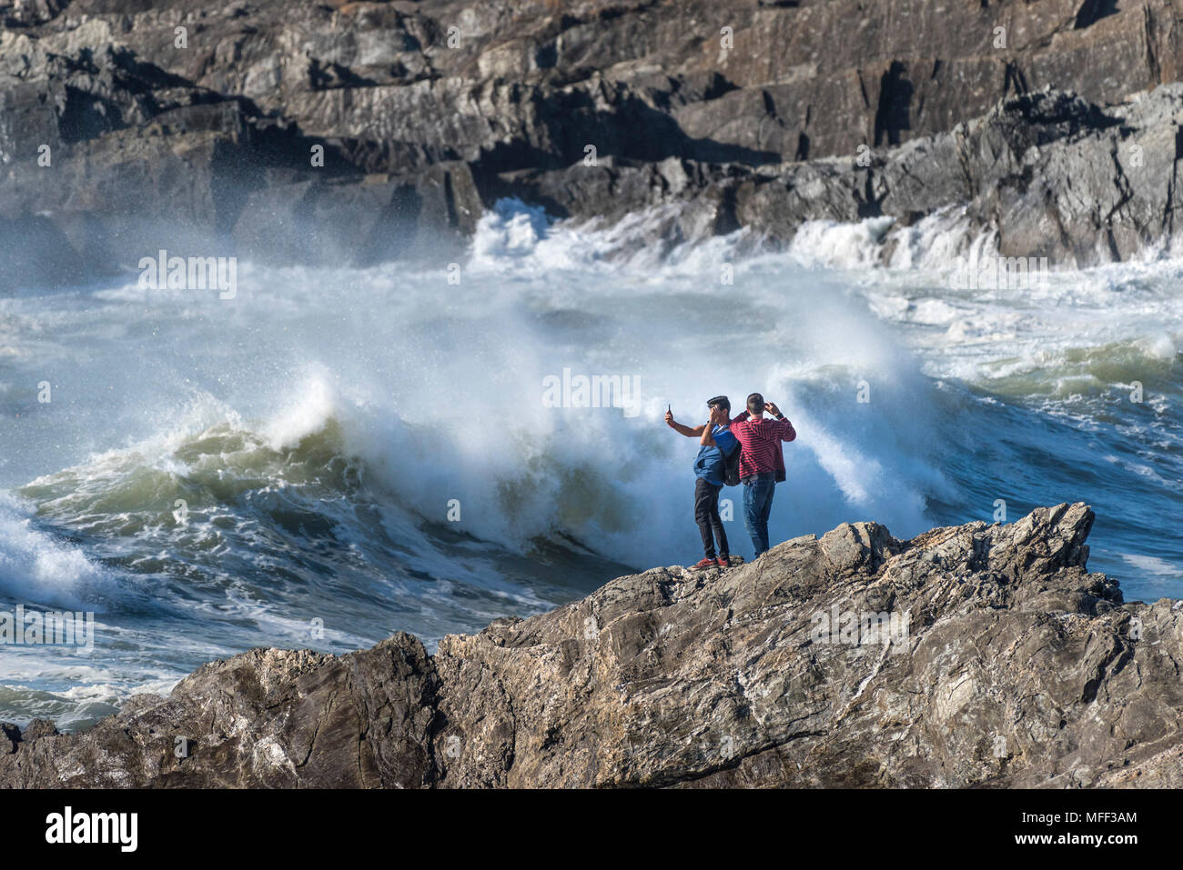 Tourists standing on rocks taking photographs as large powerful waves break on the shore at Little Fistral in Newquay Cornwall. - Stock Image