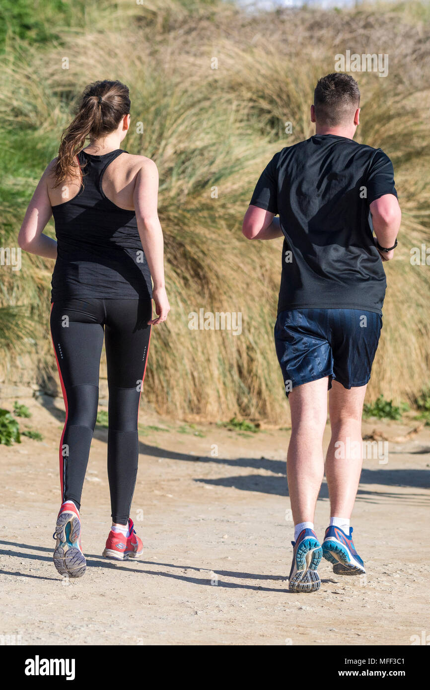 Rear view of people running on a footpath. - Stock Image