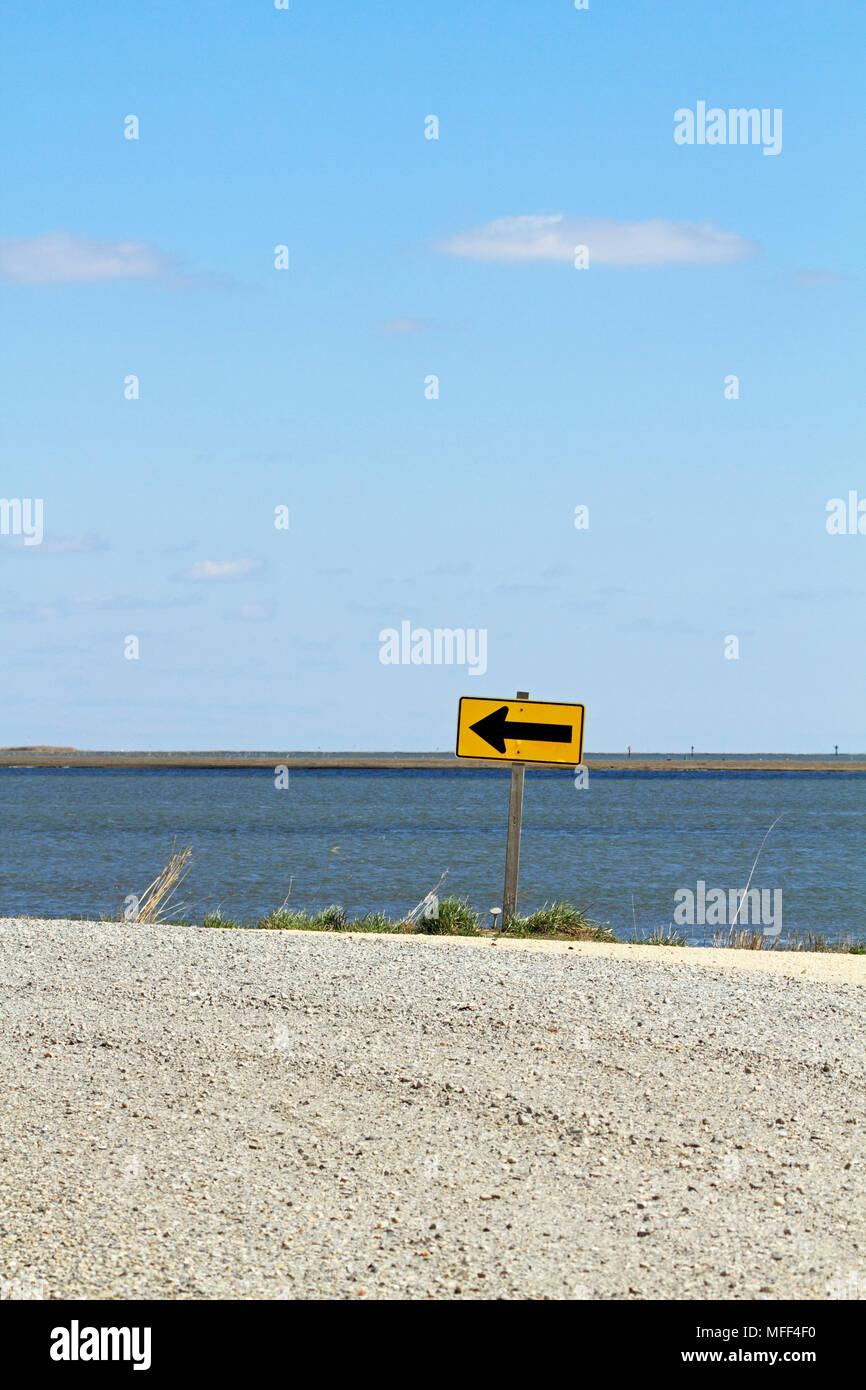 A left turn sign at the water's edge, Edwin B Forsythe National Wildlife Refuge, New Jersey, USA - Stock Image