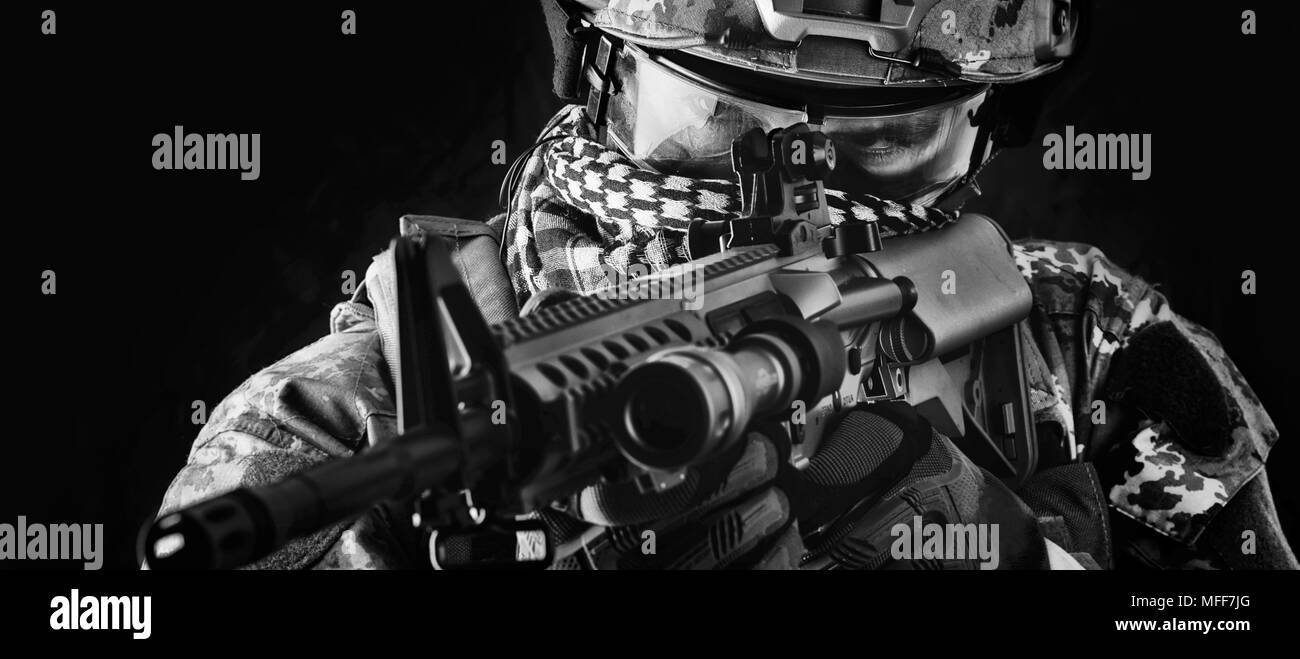 close up portrait of handsome military man. Macro shot on black background sniper with automatic rifle aiming and shooting - Stock Image