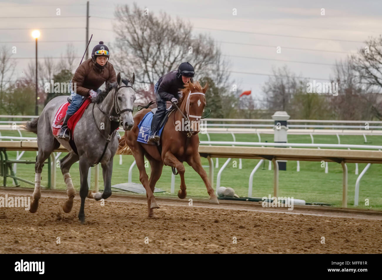 LEXINGTON, KENTUCKY/USA - APRIL 19, 2018: Two exercise riders on thoroughbreds during a workout early on a chilly morning at Keeneland Race Course. - Stock Image
