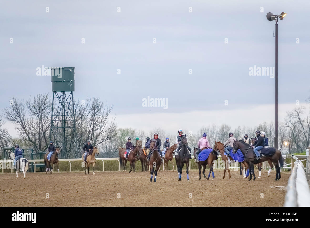 LEXINGTON, KENTUCKY/USA - APRIL 19, 2018: Riders exercise thoroughbreds singly or in pairs during a workout early on a chilly morning at Keeneland Rac - Stock Image