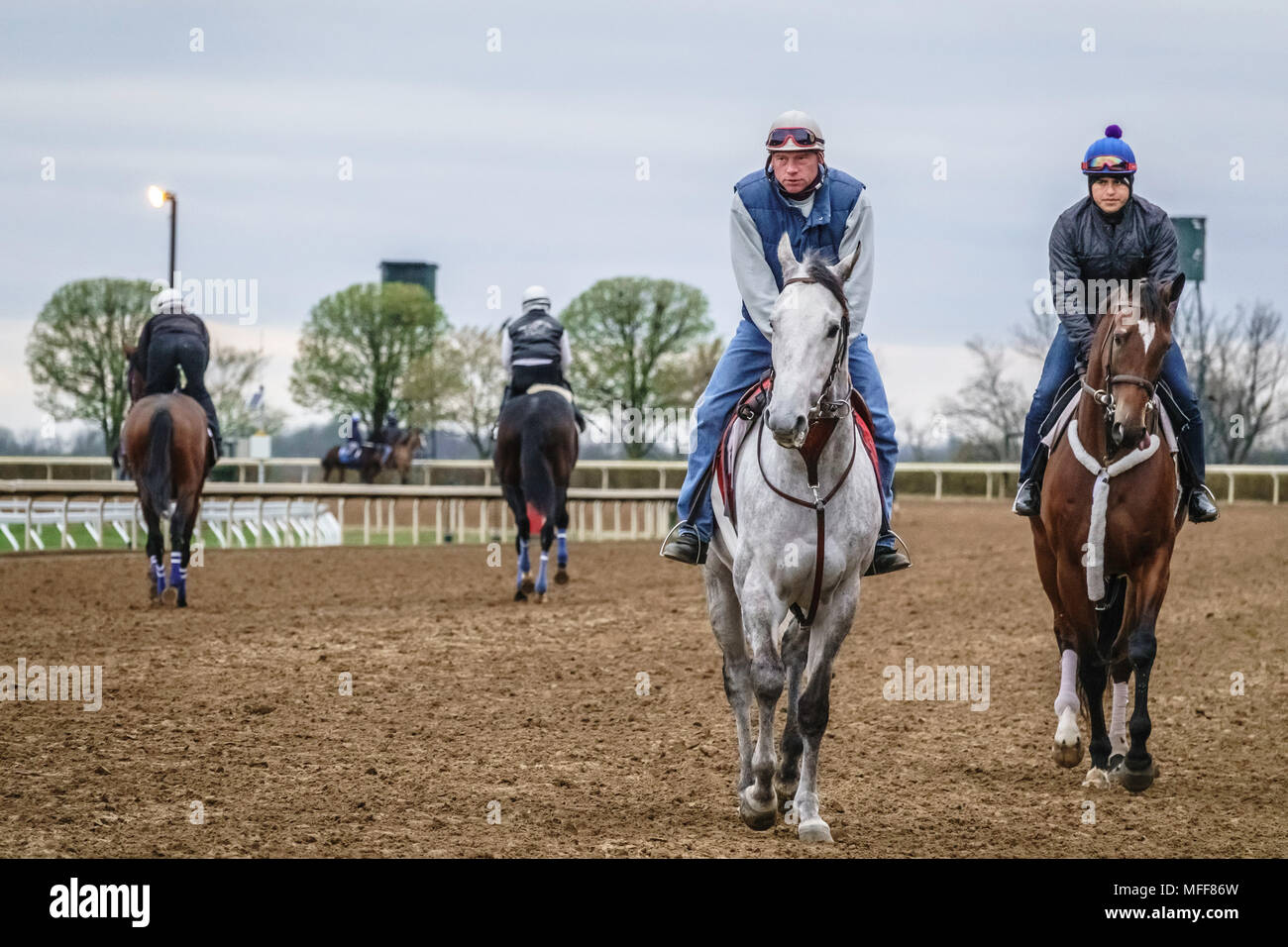 LEXINGTON, KENTUCKY/USA - APRIL 19, 2018: Exercise riders on thoroughbreds during a workout early on a chilly morning at Keeneland Race Course. - Stock Image