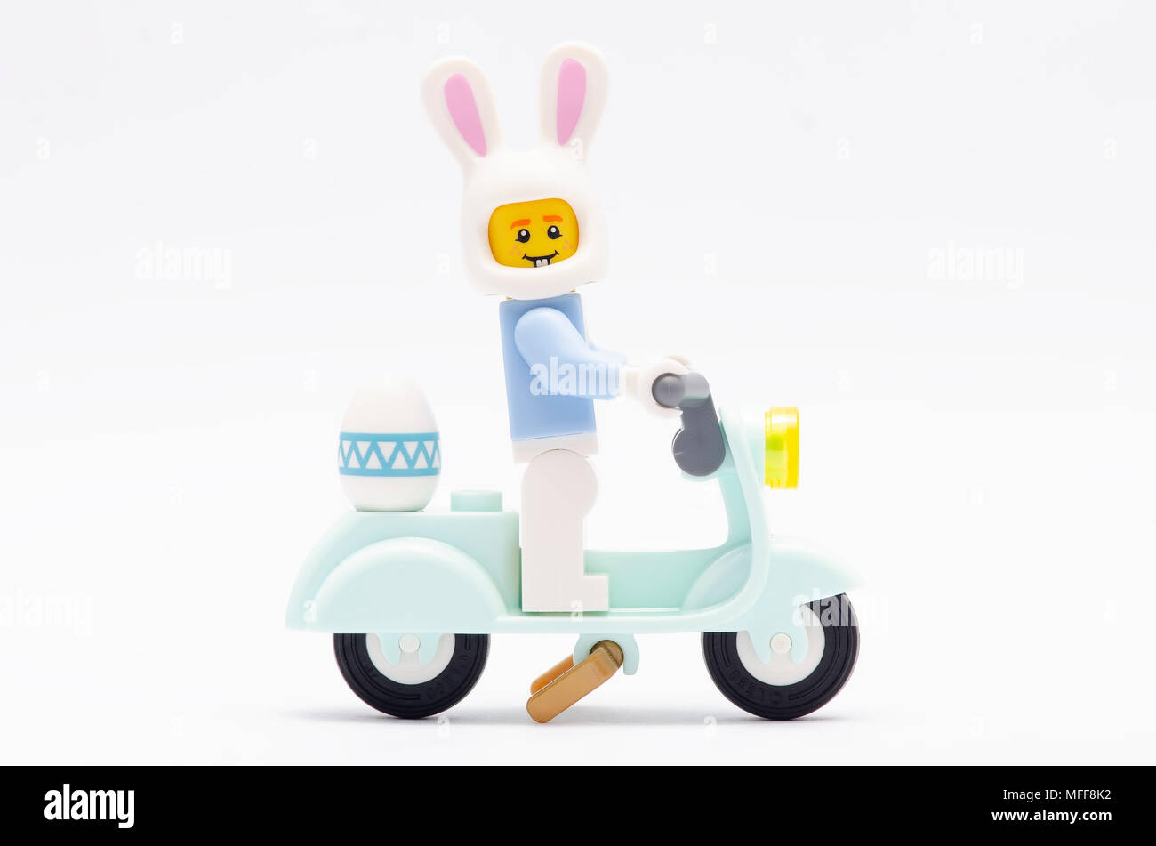 mini figure of a man wearing bunny suit riding motorcycle celebrating easter day. Lego minifigures are manufactured by The Lego Group. - Stock Image