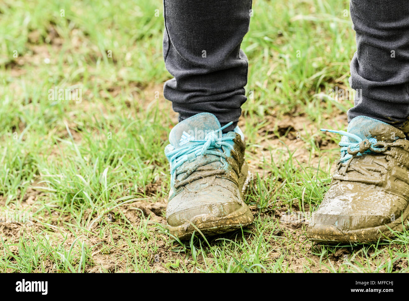On a wet field in the East Midlands countryside of England, an unfortunate child has muddied the blue shoes which are his pride and joy. - Stock Image