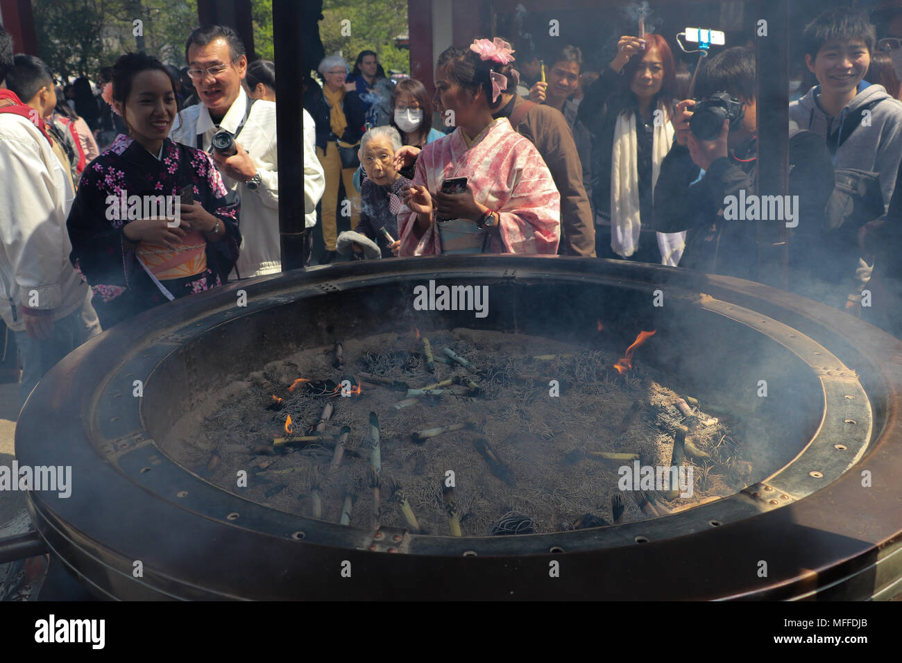 People gather around the Jokoro or incense burner at the Sensoji Temple in Tokyo, Japan. They waft the smoke over themselves, to purify, speed healing. - Stock Image