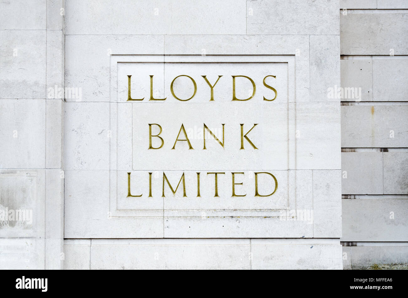 Old traditional Lloyds Bank Limited sign engraved onto stone at a brach in Coventry with gold lettering - Stock Image