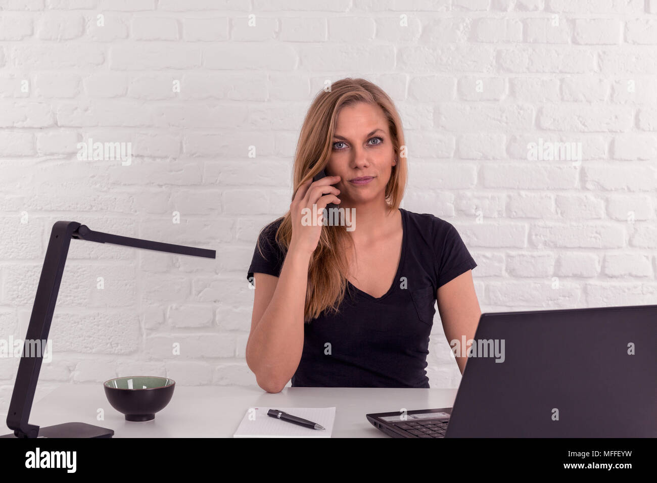 Friendly beautiful young woman at office desk with a brick wall does a phonecall - Stock Image