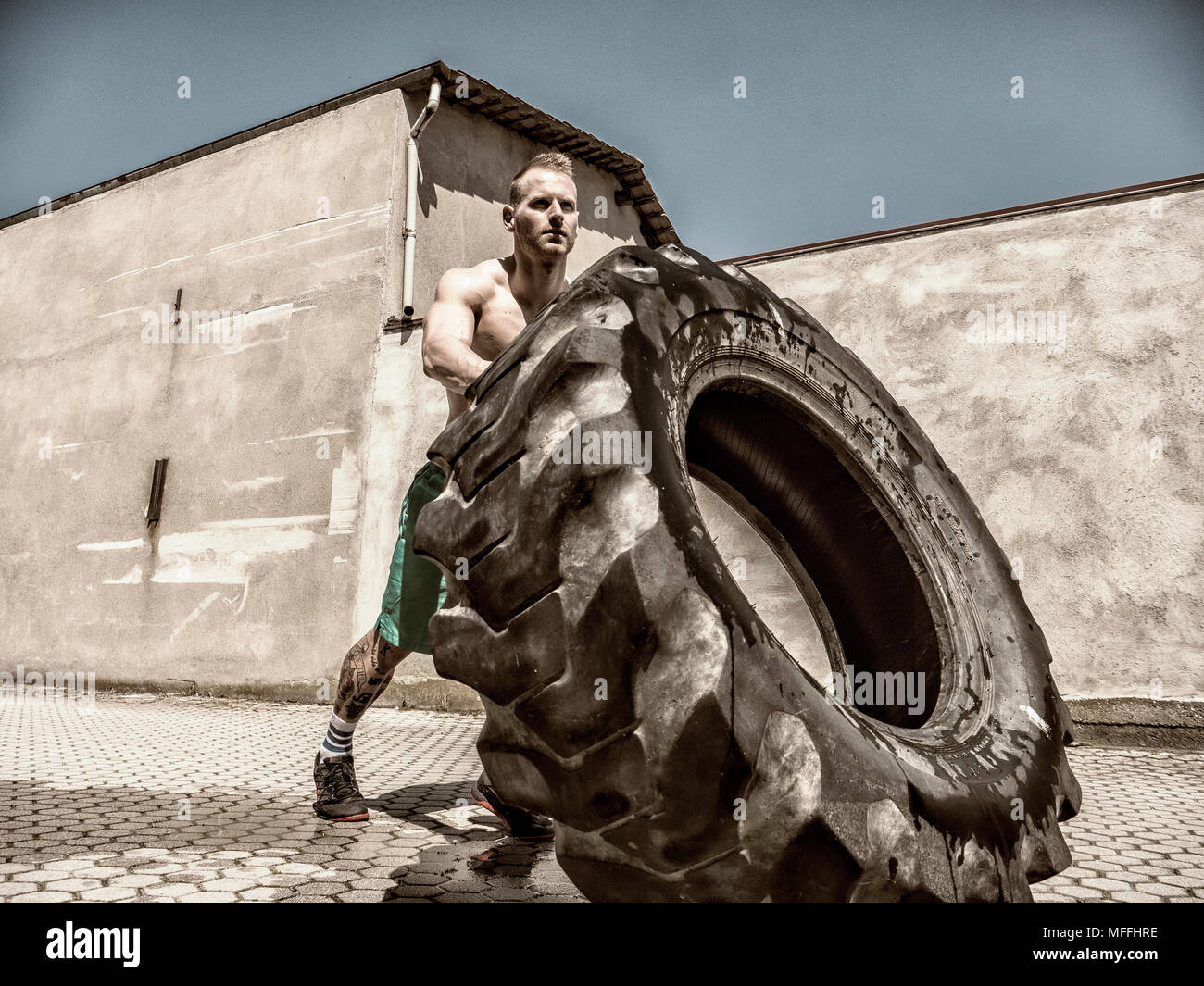 Handsome young man exercising flipping huge tire - Stock Image