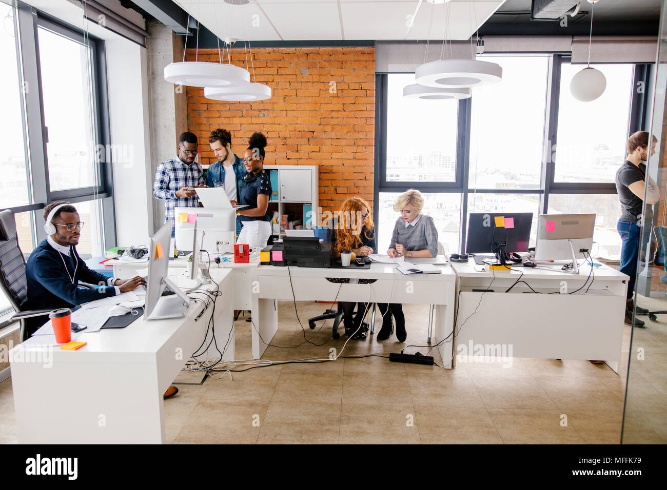 concept of altruistic activity. loft style office is full of young ambitious volunteers - Stock Image