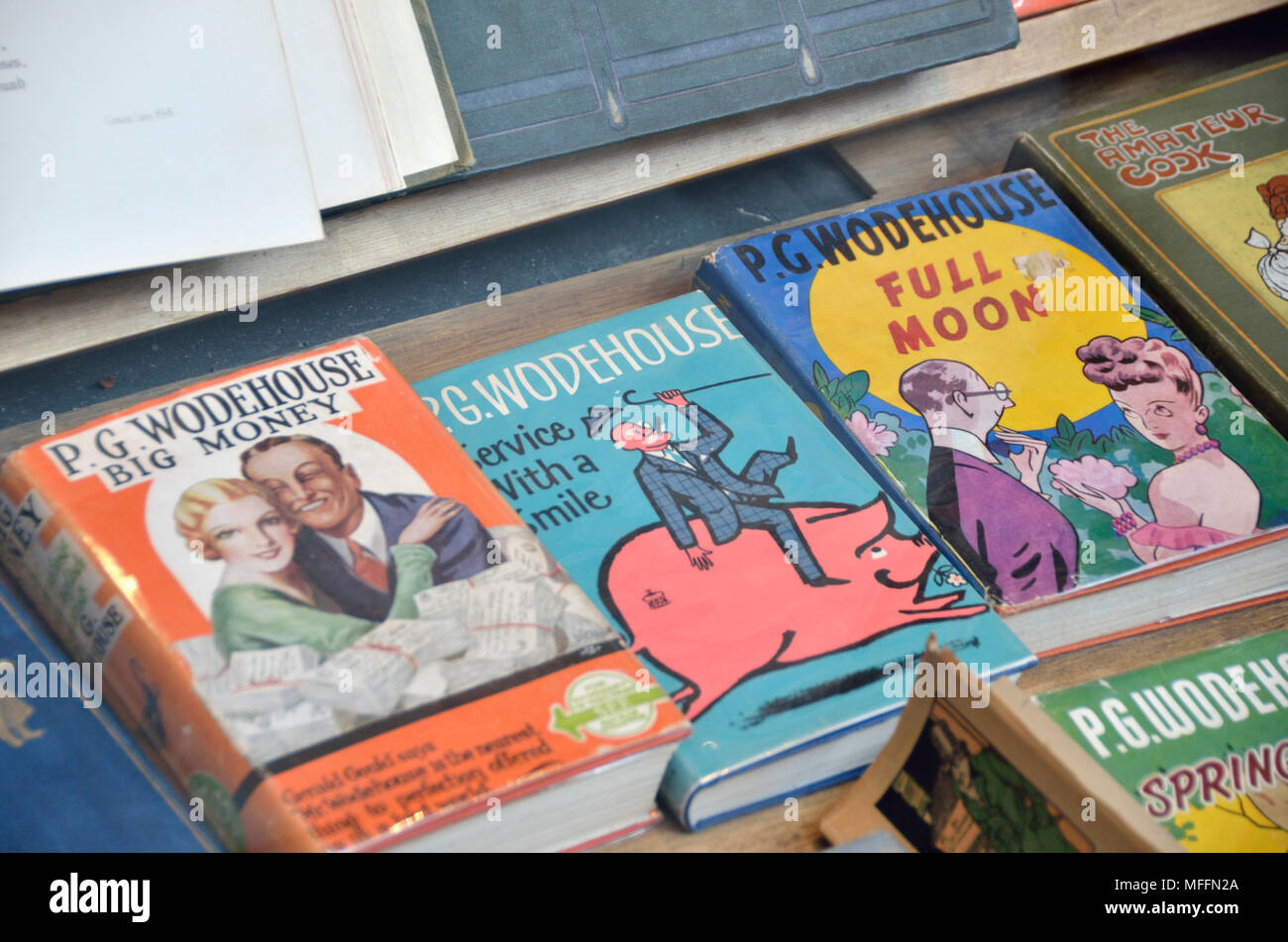 Old secondhand copies of P G Wodehouse novels in a bookshop window display. - Stock Image