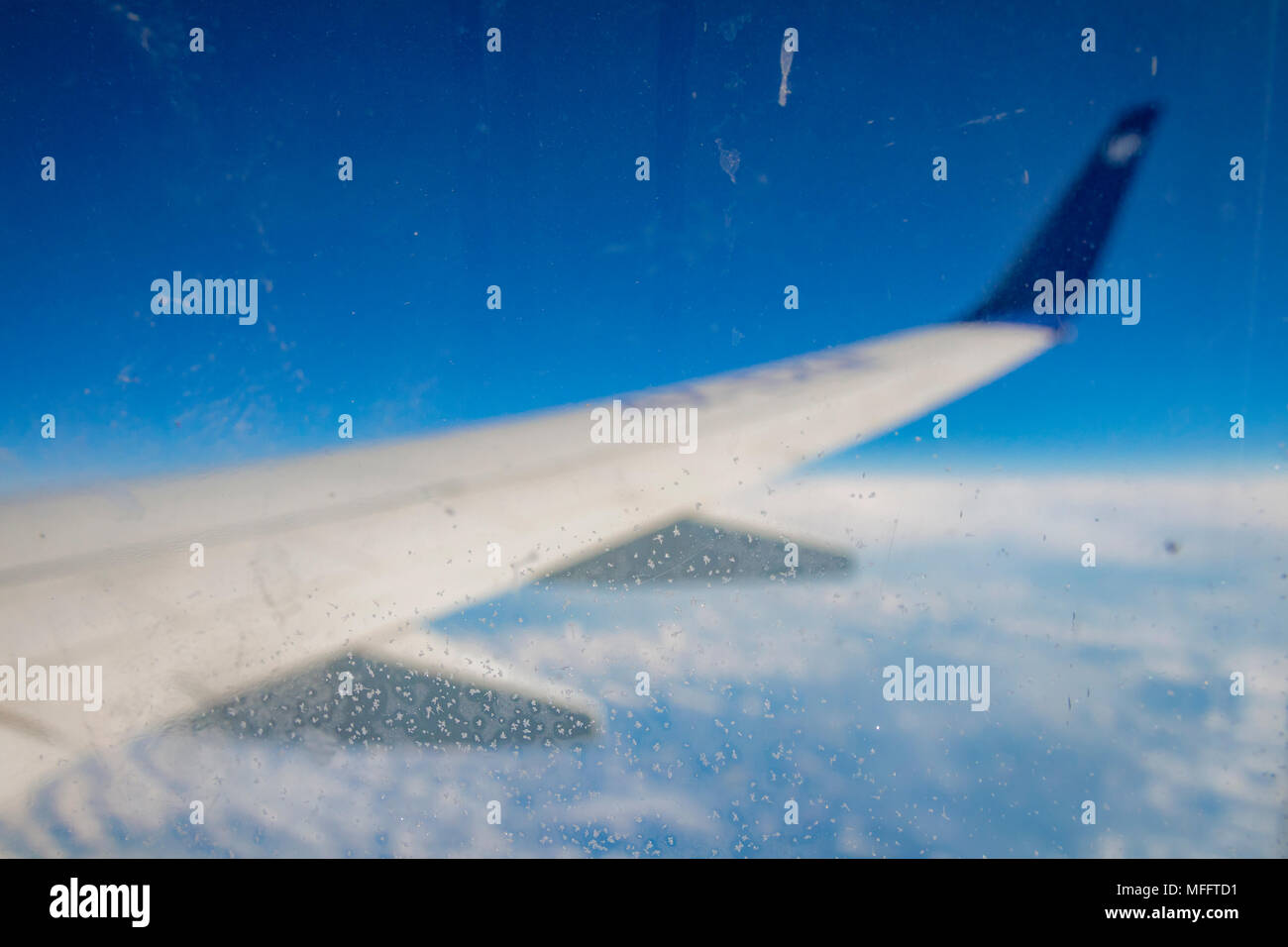 Frozen condensation of ice crystals on the window of an airplane with the wing in the back. - Stock Image