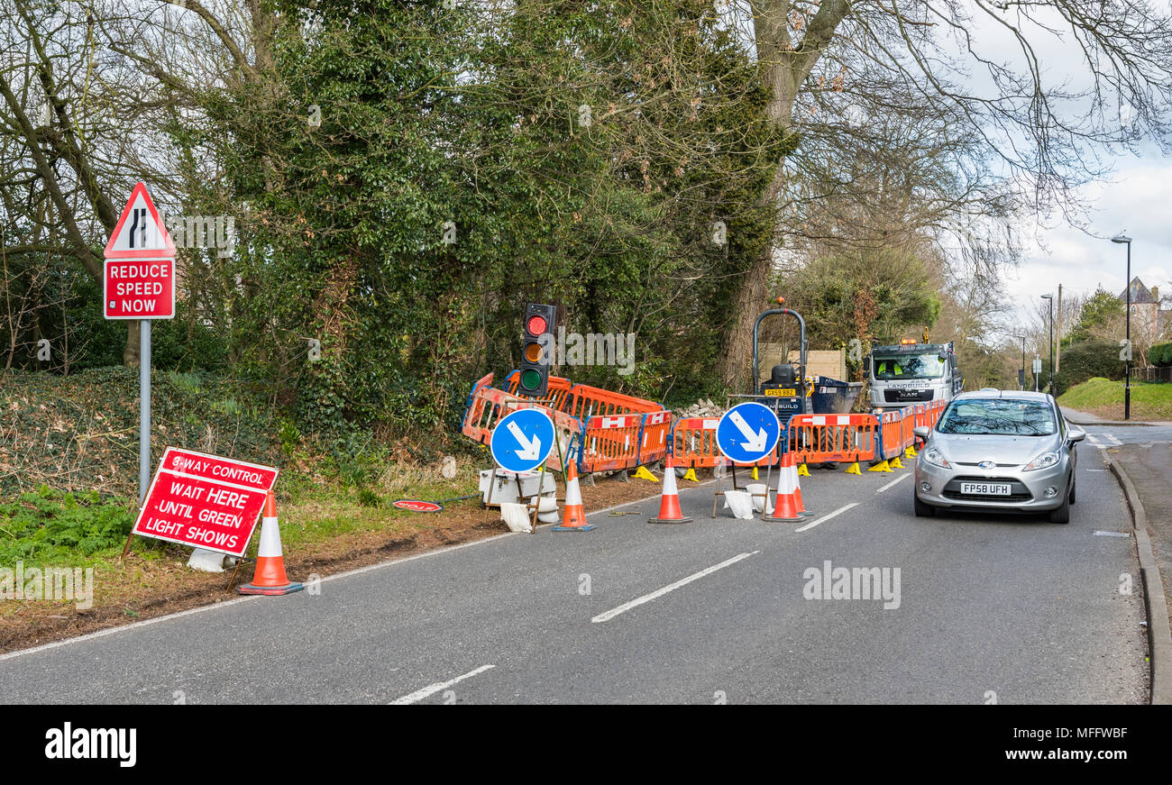 Temporary traffic lights at temporary roadworks blocking one lane of traffic in the UK. - Stock Image