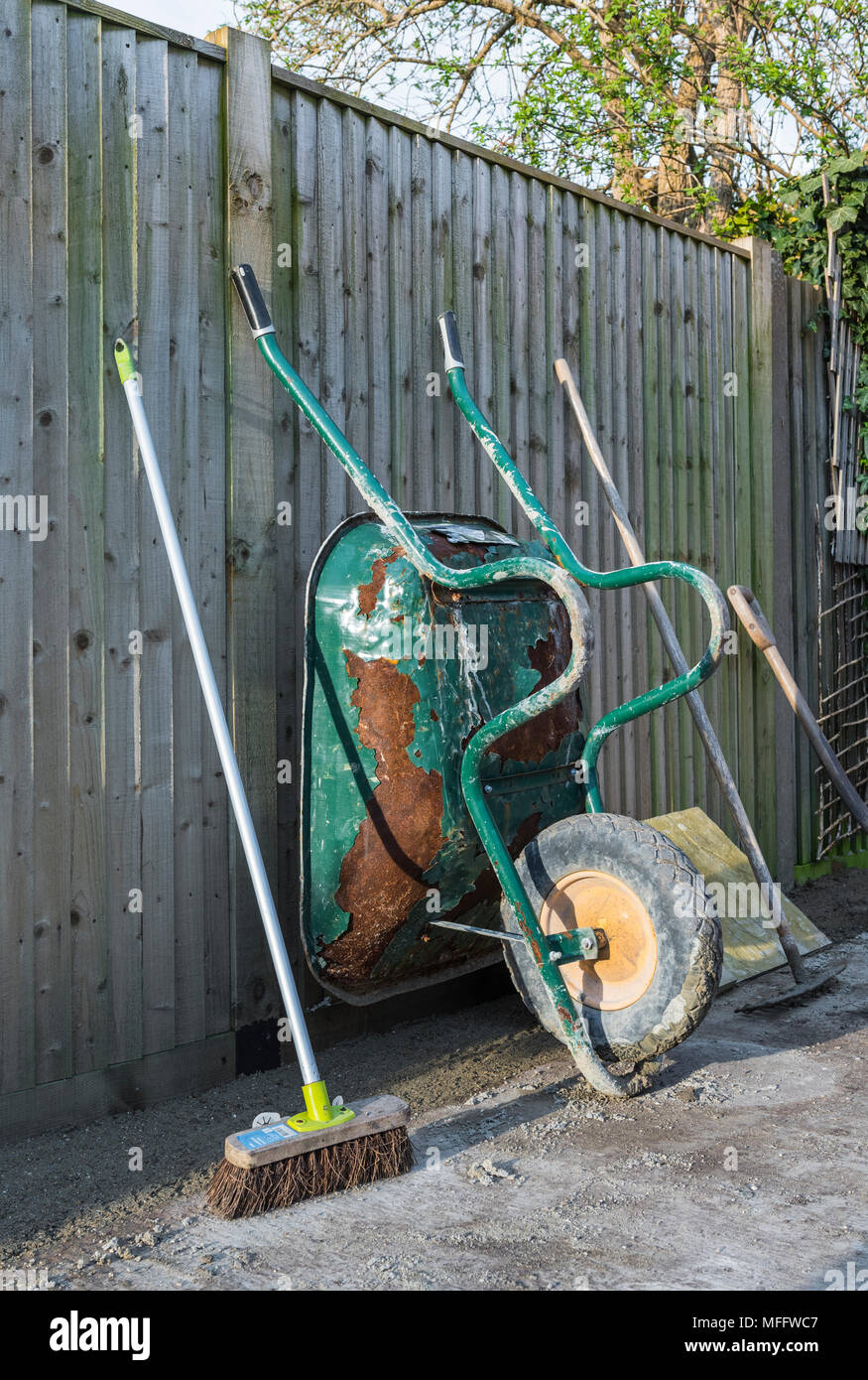 Wheelbarrow and other garden tools leaning on a fence at the end of a work day during construction work in a back garden or back yard. - Stock Image