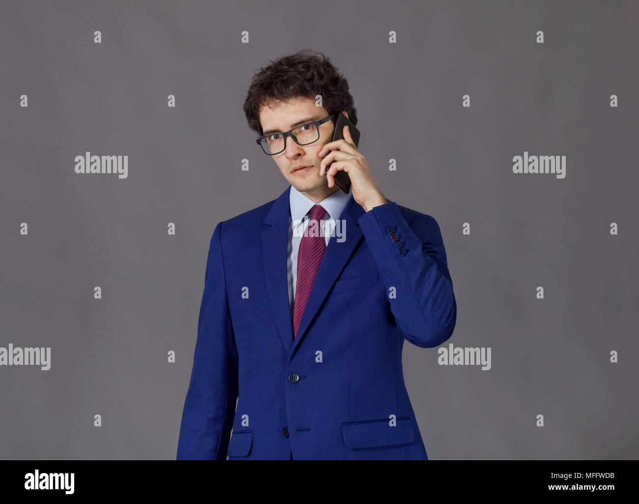 Curly-headed man wearing in blue jacket and glasses talking by mobile phone - Stock Image