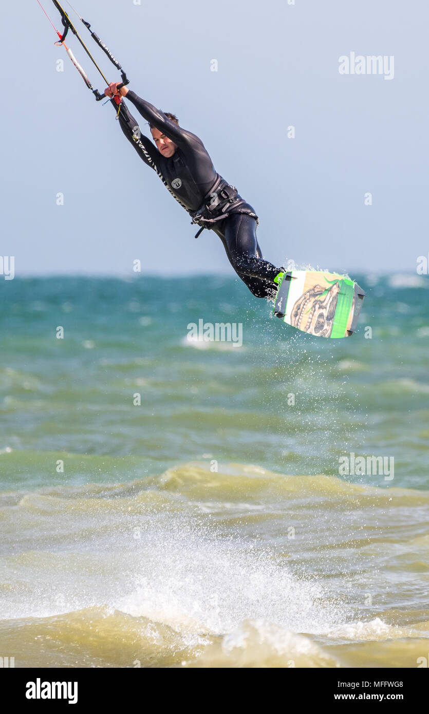 Man performing a stunt while kitesurfing at sea, flying in the air. Portrait view. - Stock Image