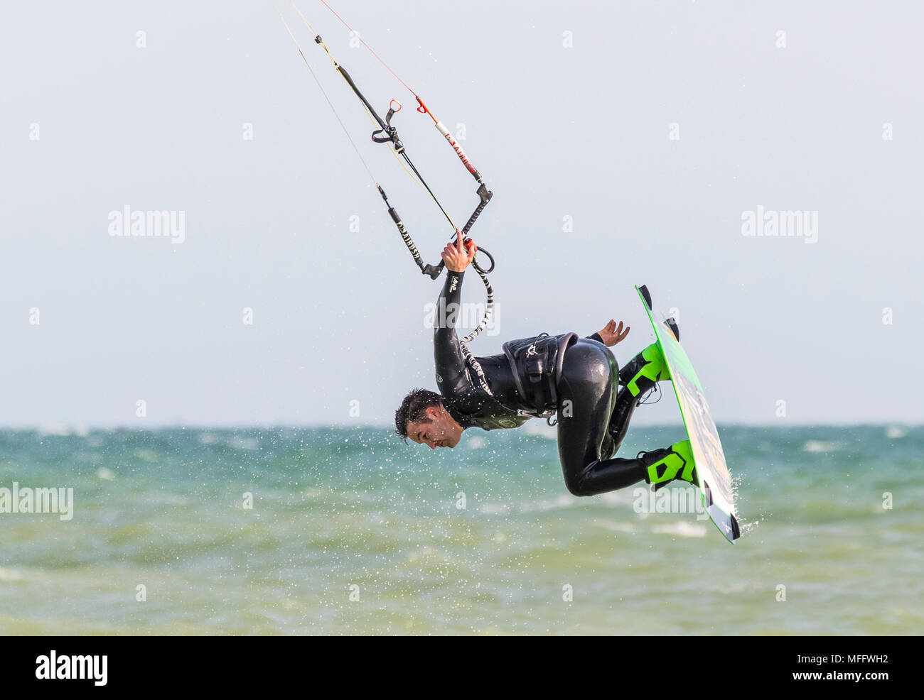 Man kitesurfing at sea while in the air in a spin, holding on with one hand. Kitesurfer on the ocean. - Stock Image