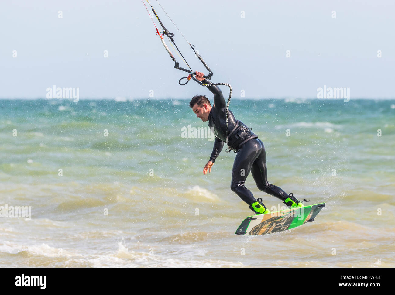 Man kitesurfing at sea and taking off while holding on with one hand. Kitesurfer on the ocean. Watersports. - Stock Image