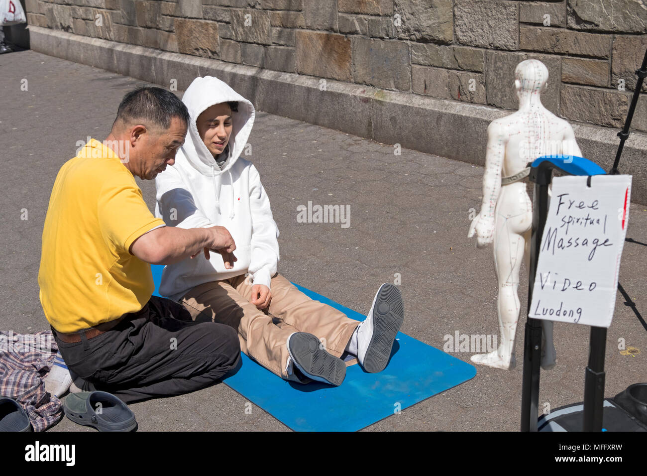 Luo Dong giving a free spiritual massage to a young lady in a hooded sweatshirt. In Union Square Park, Manhattan, New York City. - Stock Image