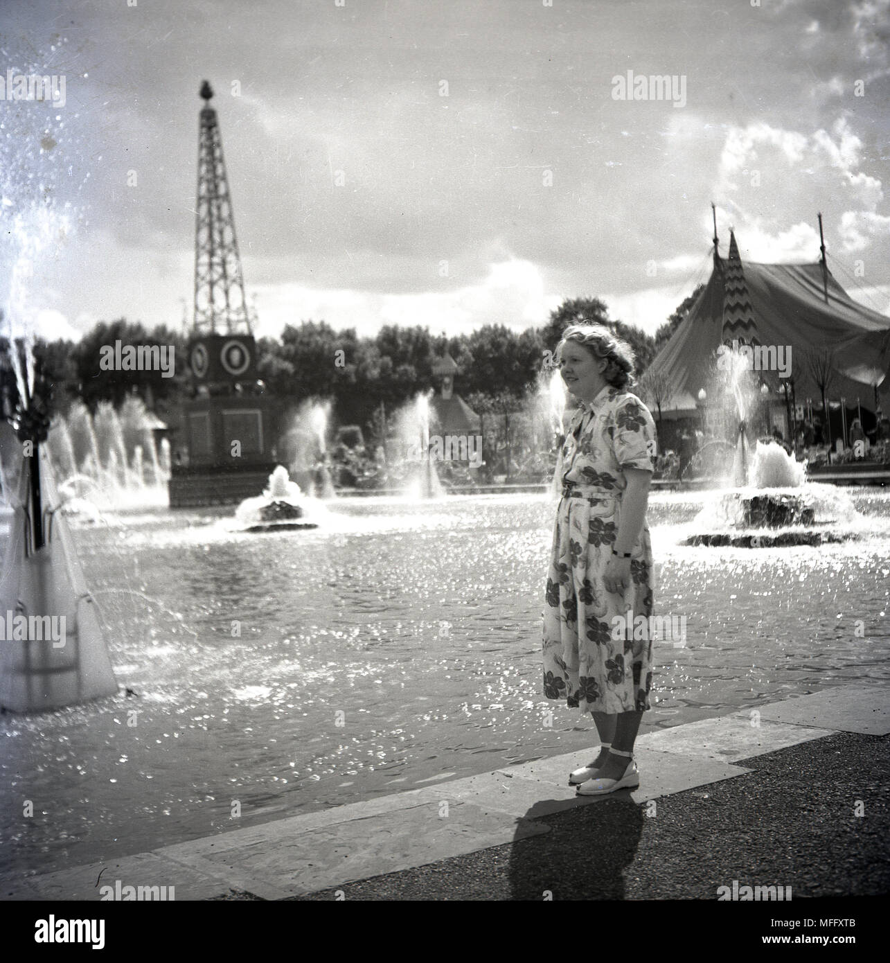 1951, historical, lady in a flowery dress standing by a water display with fountains at the Festival of Britain, Battersea Park, London, England, UK. The idea behind the festival was celebrating British industry, arts and science and inspiring the thought of a better Britain following the harshness of the post-ww2 era. - Stock Image