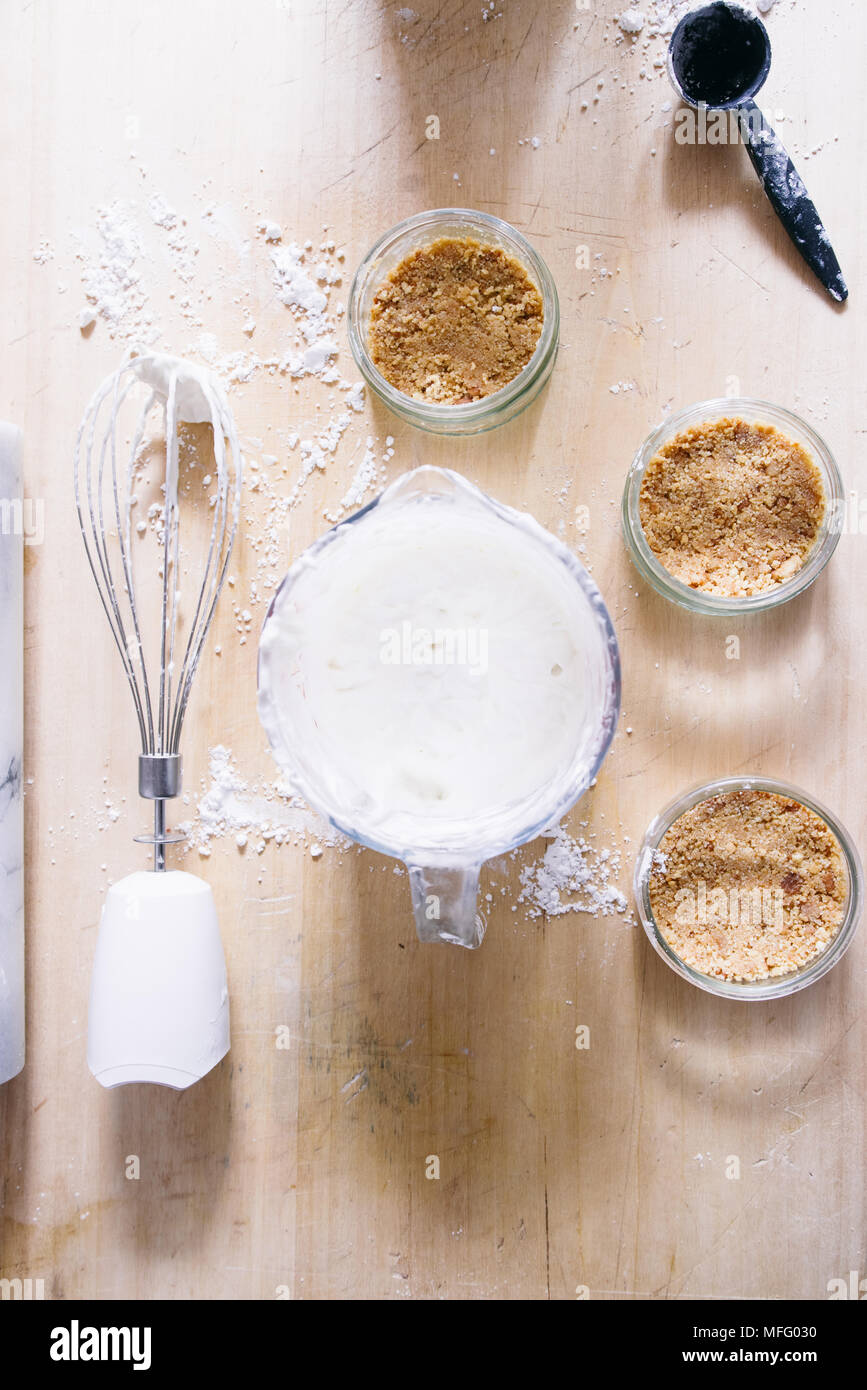 Preparation of a cheesecake on jar without baking it, biscuit mixed with butter are pressed in glass container - Stock Image